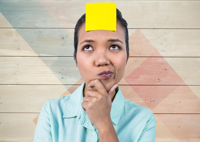 Frustrated woman with sticky note stuck on her head against wooden background royalty free stock images