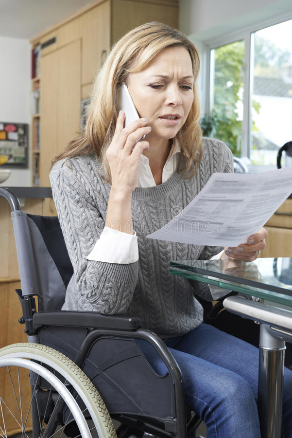 Frustrated Woman In Wheelchair Making Phone Call Whilst Reading. Frustrated Woman In Wheelchair Making Phone Call And Reading Letter stock images