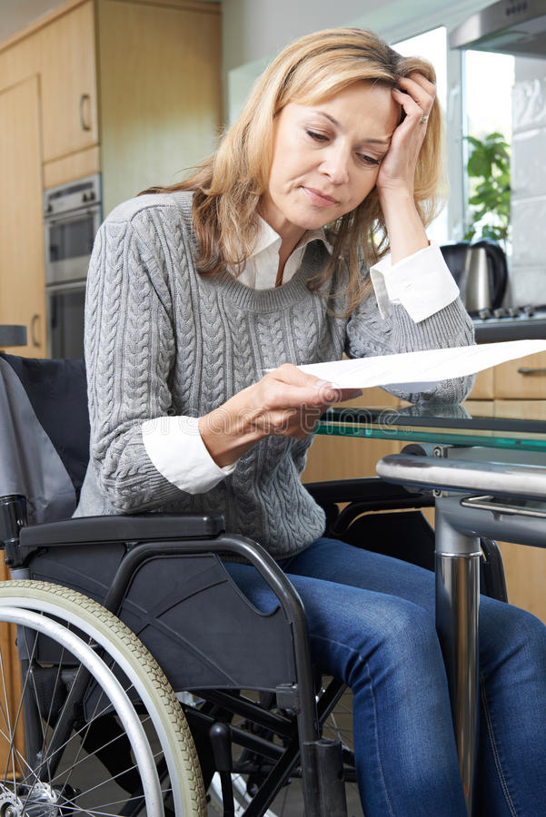 Frustrated Woman In Wheelchair Reading Letter. Frustrated Woman In Wheelchair Reads Letter stock image
