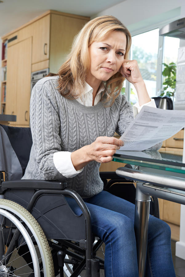 Frustrated Woman In Wheelchair Reading Letter. Frustrated Woman In Wheelchair Reads Letter royalty free stock image