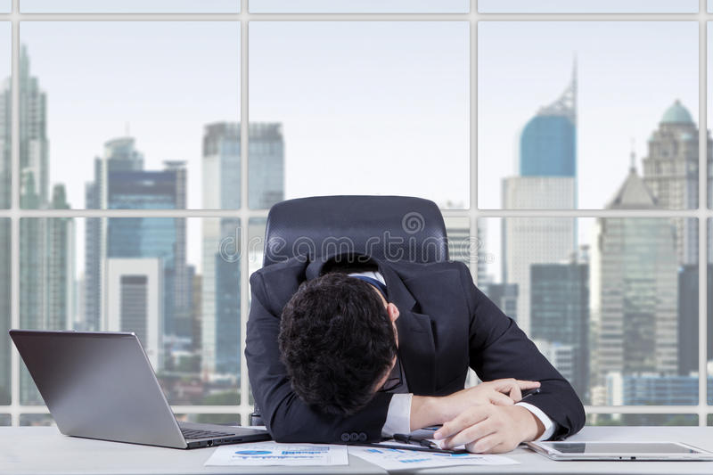 Frustrated worker sleeping in the office royalty free stock photography