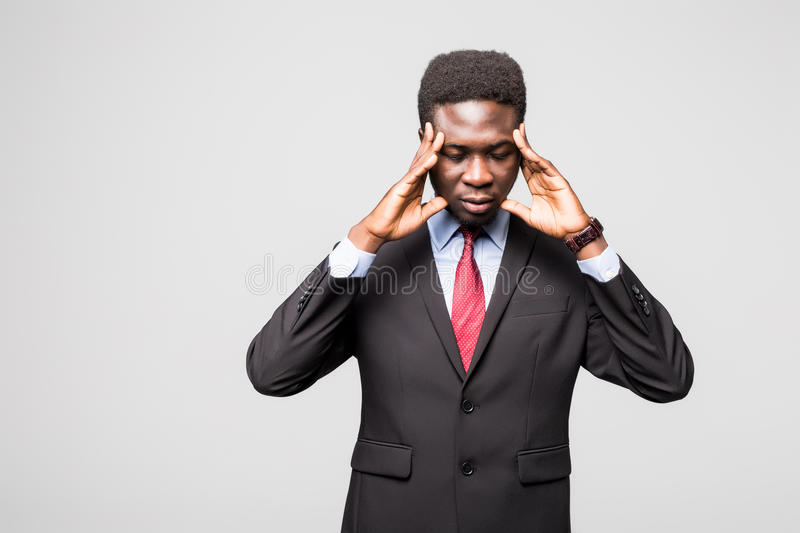 Frustrated young African man holding fingers on head and looking at camera while standing against grey background. Feeling upset. Young African man in formalwear royalty free stock image