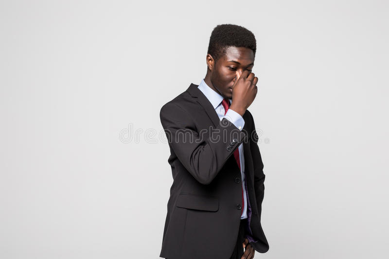 Frustrated young African man massaging nose and keeping eyes closed while standing against grey background royalty free stock photography