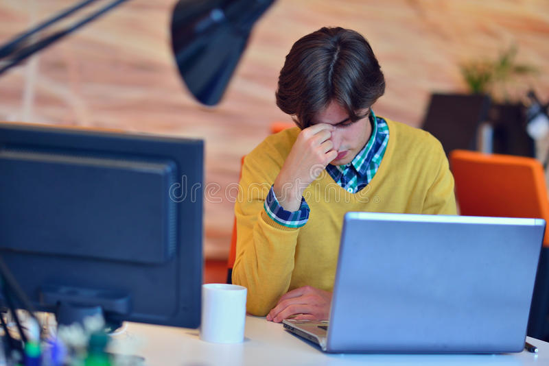 Frustrated young business man working on desktop computer at startup office stock photo