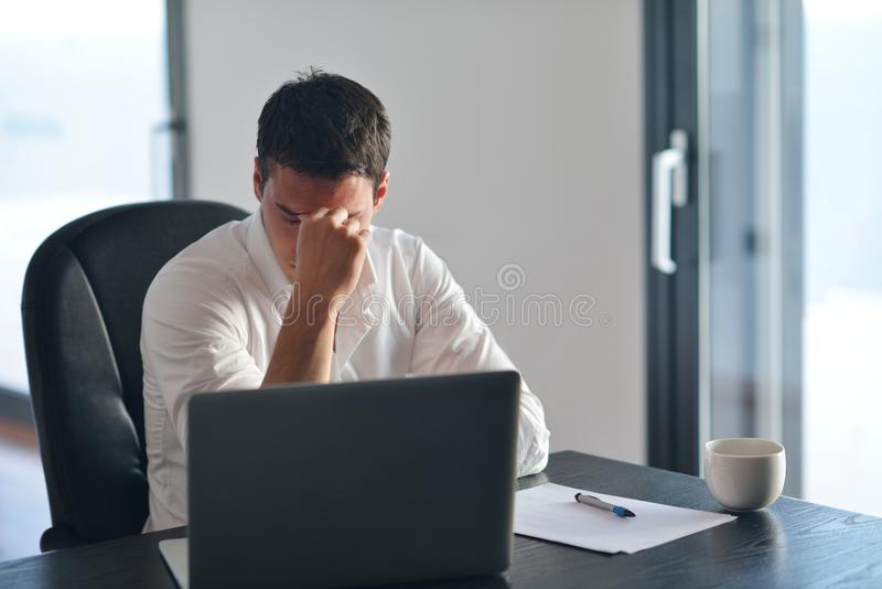 Frustrated young business man working on laptop computer at home royalty free stock image