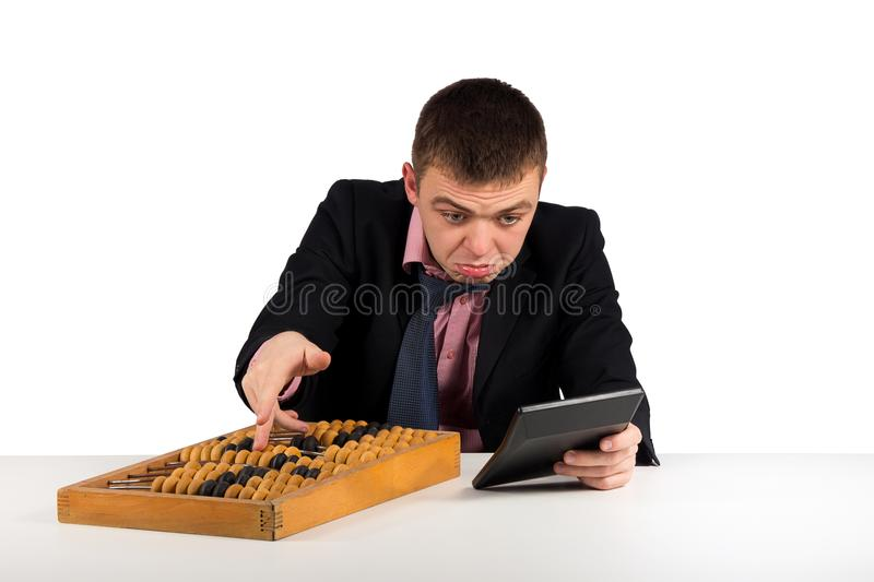 Frustrated young businessman with calculator and abacus royalty free stock image
