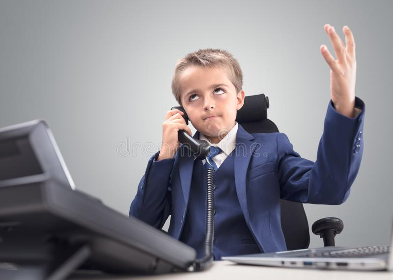 Frustrated young child businessman despair and disappointment on the telephone. Frustrated and stressed young child businessman despair and disappointment on the stock images