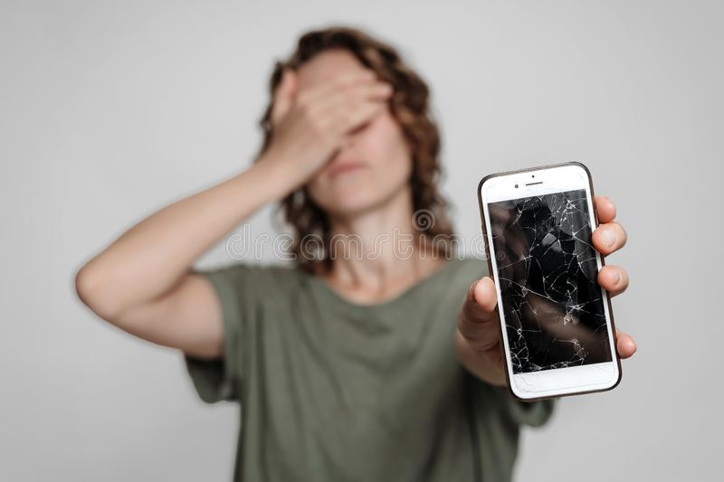 Frustrated young curly woman holding smartphone with broken screen glass. Phone display needs to repair. Isolated on gray background stock photos