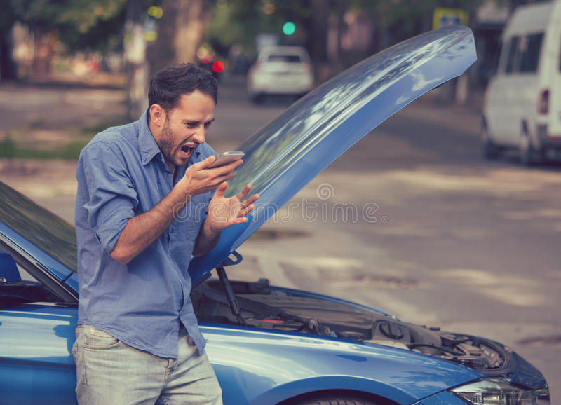 Frustrated young man calling roadside assistance after breaking down royalty free stock image