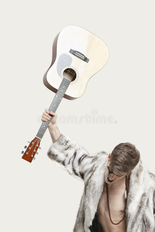 Download Frustrated Young Man In Fur Coat About To Throw His Guitar Against Gray Background Stock Image - Image: 30854667