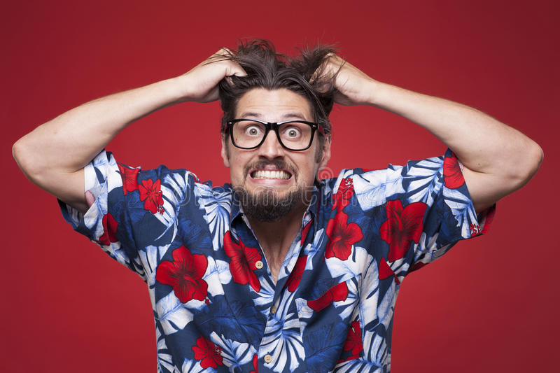 Frustrated young man in Hawaiian shirt pulling his hair stock image