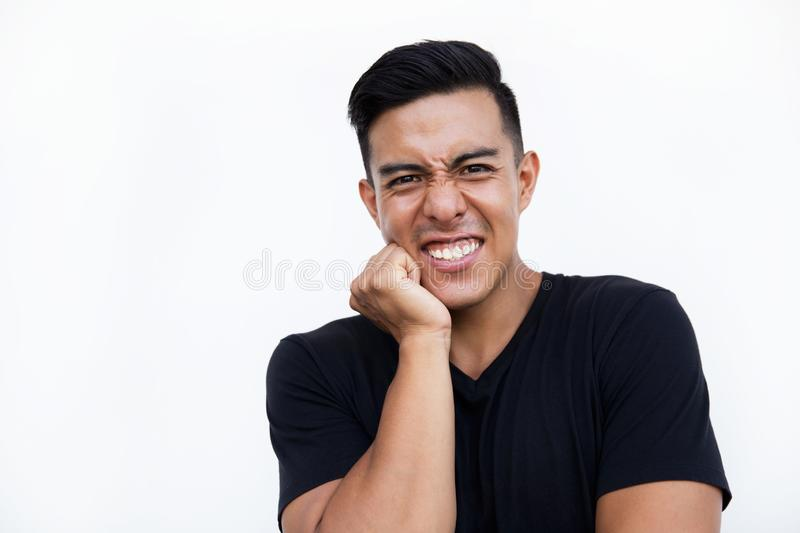 Young man holding hand on his cheek while standing on white background. stock photo