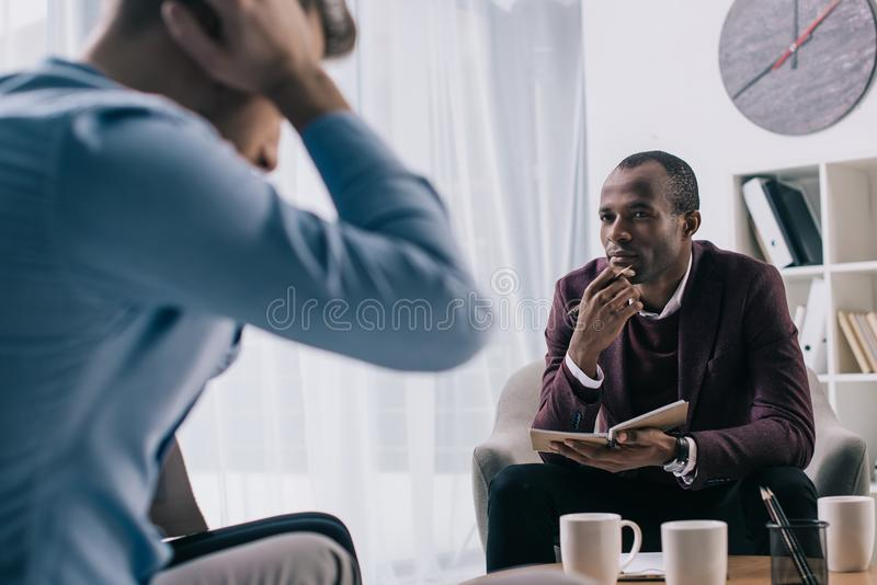 Frustrated young man sititng on sofa and african american psychiatrist. Frustrated young men sititng on sofa and african american psychiatrist in office royalty free stock photo