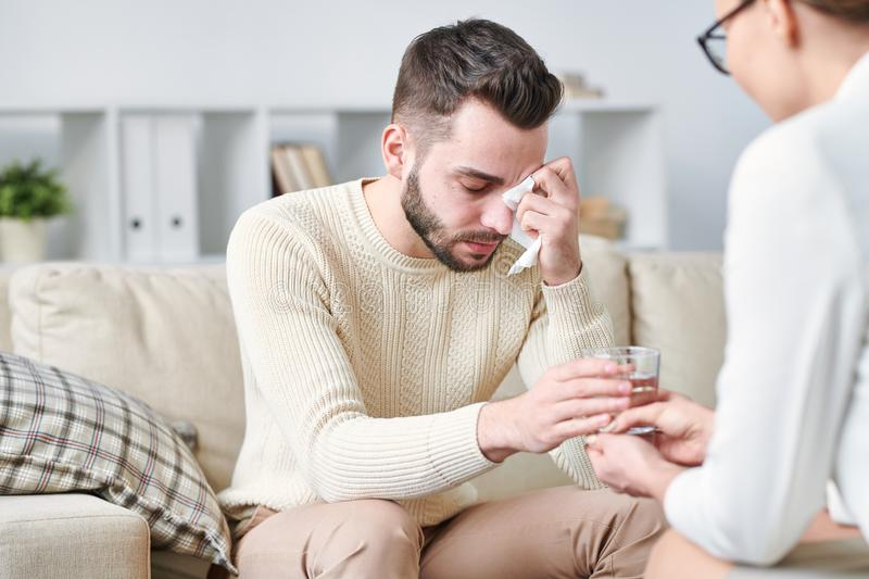 Frustration. Frustrated young men taking glass of water from hand of counselor while sitting on couch and wiping tears with tissue stock photo