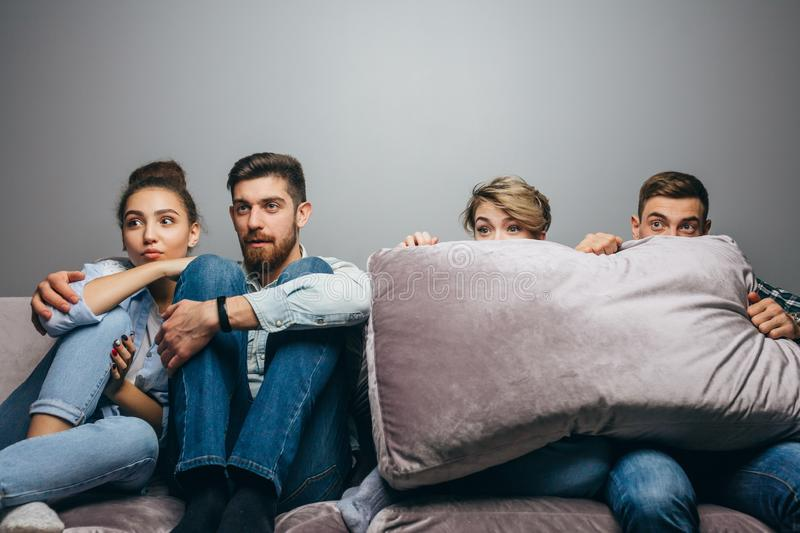 Frustrated young men and women are sitting in fron of Tv. Close up photo. fear, fobia, emotion, feeling stock photography