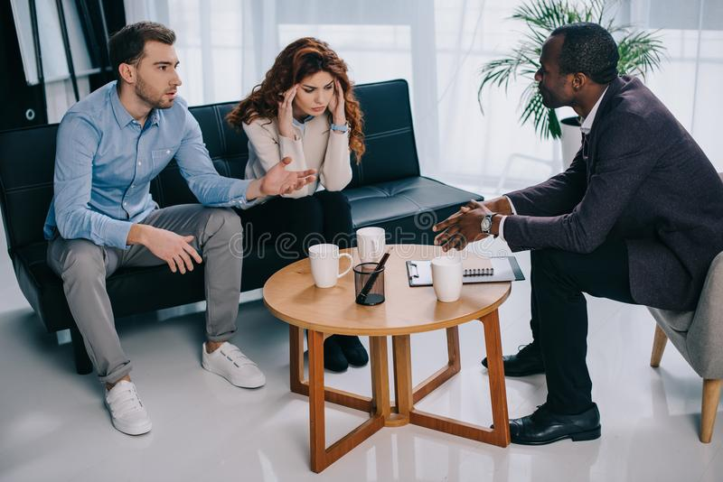 Frustrated young woman with boyfriend and african american counselor royalty free stock photo