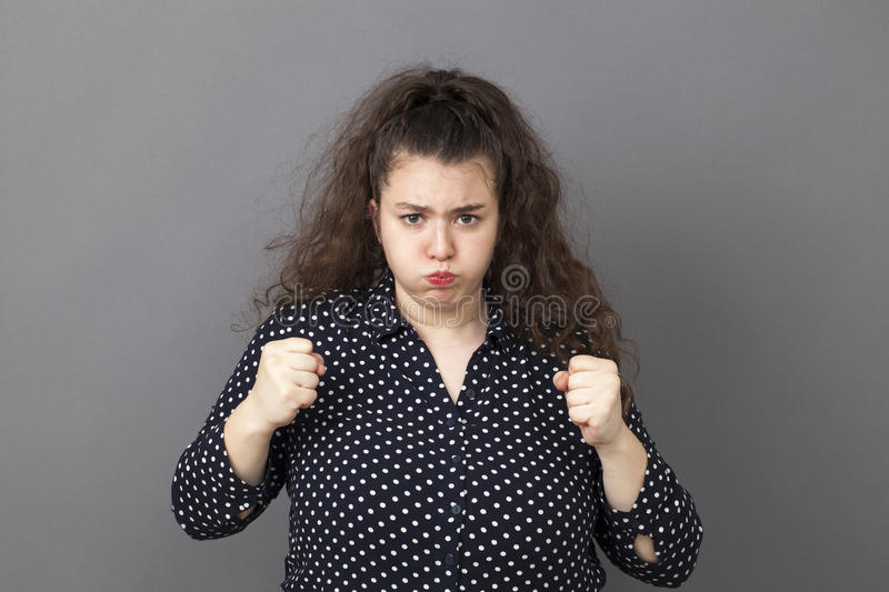 Frustrated young woman pouting for frustration. Puffing overweight 20's woman expressing exasperation and frustration with both fists and mouth ready to explode stock image