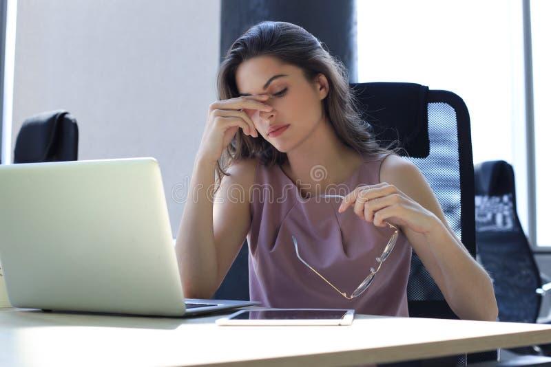 Frustratie zakenvrouw die er uitgeput uitziet terwijl ze op haar werkplek zit en haar bril in de hand draagt stock afbeeldingen
