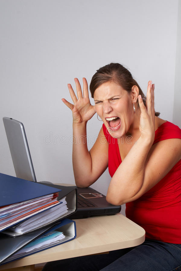 Frustrating. Young woman sitting at her laptop with a lot of work in front of her. She is very frustrated stock photos