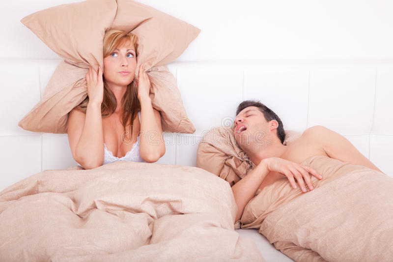 Frustrating couple. Scenic in bedroom of pair of loving with young couple lying in bed and holding pillow on the ears because of snoring boyfriend