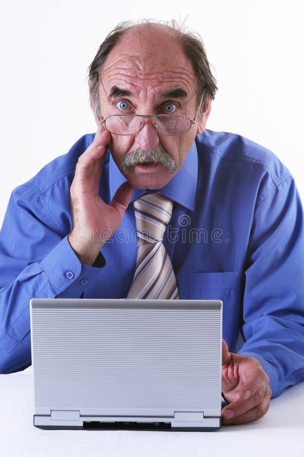 Frustration. A mature businessman howls in frustration at his laptop stock photos