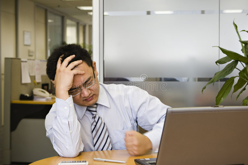 Frustration. Asian business executive shows frustration at work royalty free stock photography