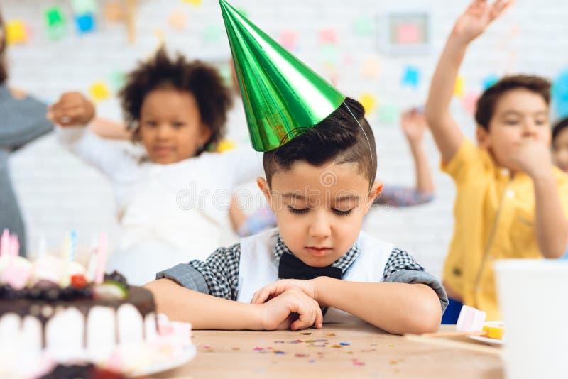 Frustreerde weinig jongen in groene feestelijke hoed zit bij lijst met cake bij verjaardag royalty-vrije stock afbeeldingen