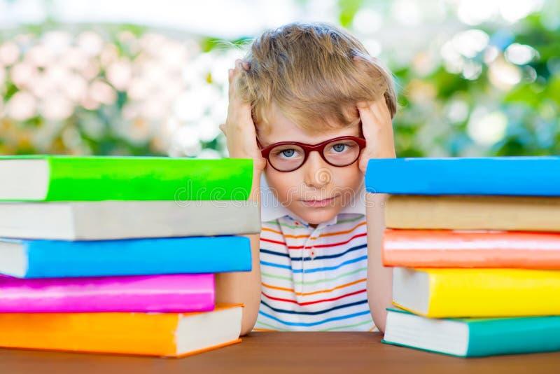 Frustreerde weinig schooljongen met glazen en boeken royalty-vrije stock foto's