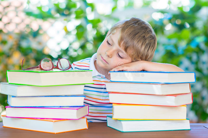 Frustreerde weinig schooljongen met glazen en boeken royalty-vrije stock fotografie