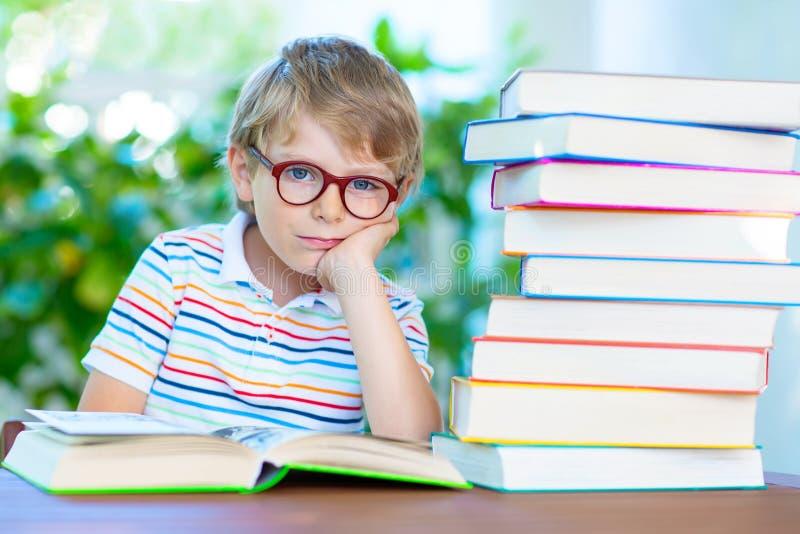 Frustreerde weinig schooljongen met glazen en boeken royalty-vrije stock foto