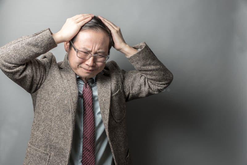 Frustrera den asiatiska affärsmannen royaltyfri bild