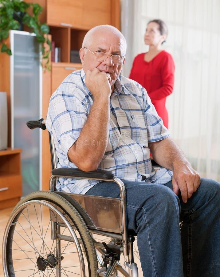 Frustrerad äldre make i rullstol bredvid fru arkivfoton