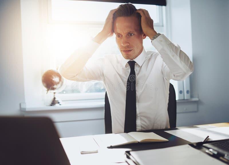Frustrerad affärsman som ser bärbara datorn arkivbild