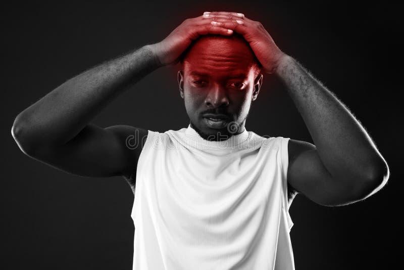 Frustrerad afrikansk man som trycker på hans huvud arkivfoto