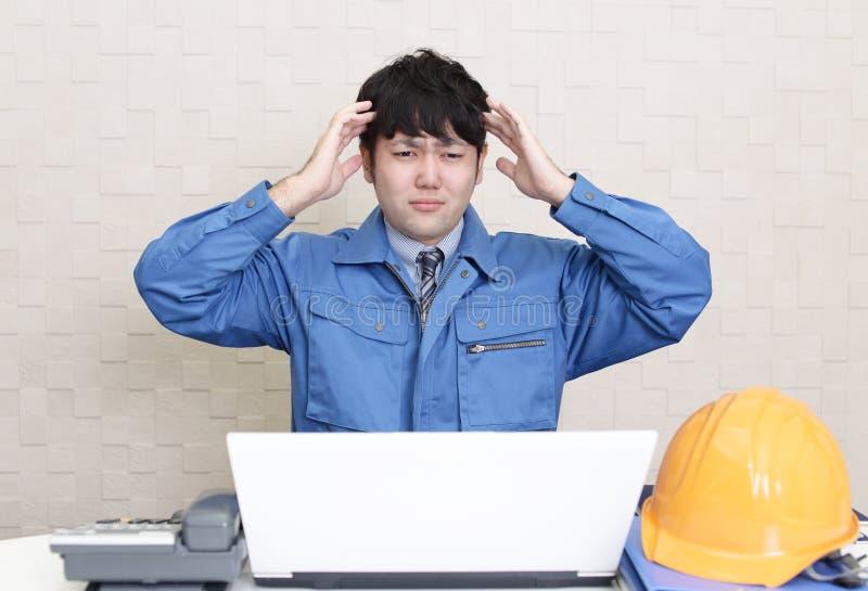 Frustrerad asiatisk arbetare arkivfoto