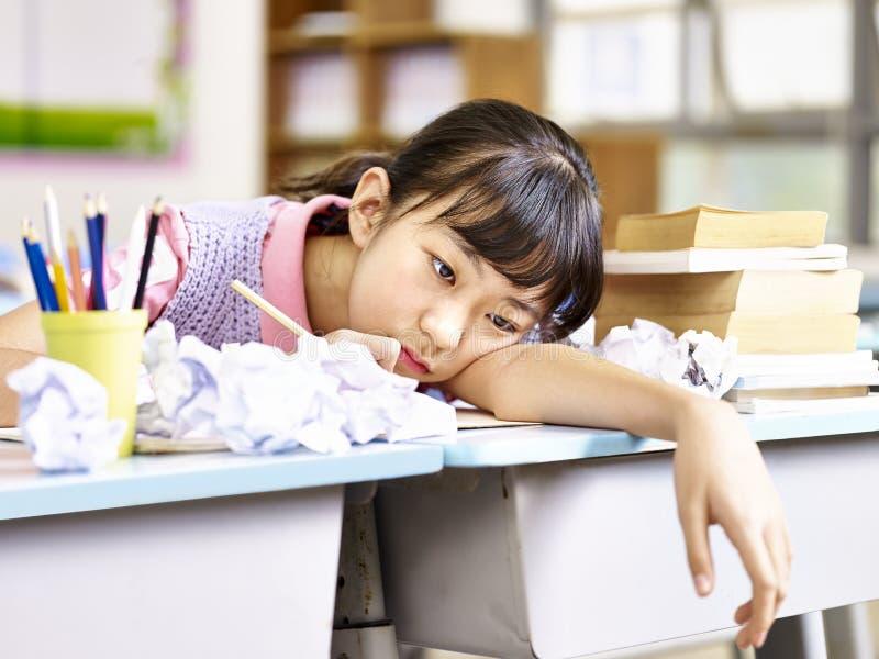 Frustrerad asiatisk grundskolaflicka royaltyfri foto