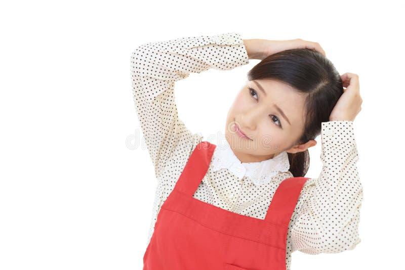 Frustrerad asiatisk hemmafru fotografering för bildbyråer