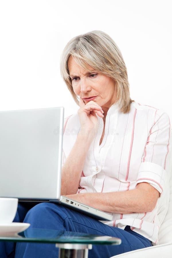 frustrerad bärbar datorpensionärkvinna arkivfoto