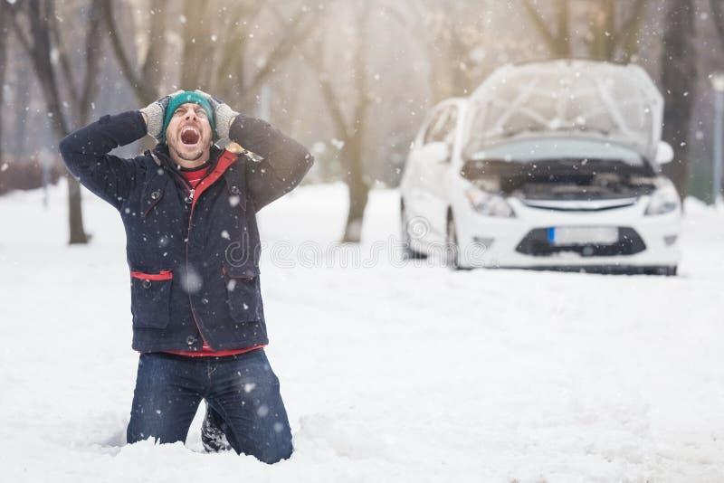 Frustrerad chaufför bredvid den brutna bilen Övervintra problem för säsongvägturen och hjälpbegreppet royaltyfria foton