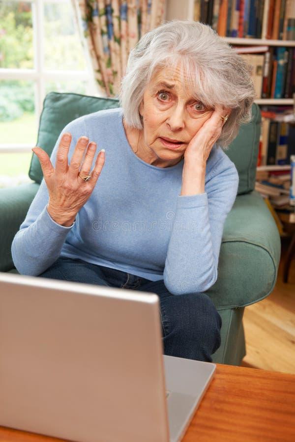 Frustrerad hög kvinna som försöker att använda bärbar datordatoren royaltyfria bilder