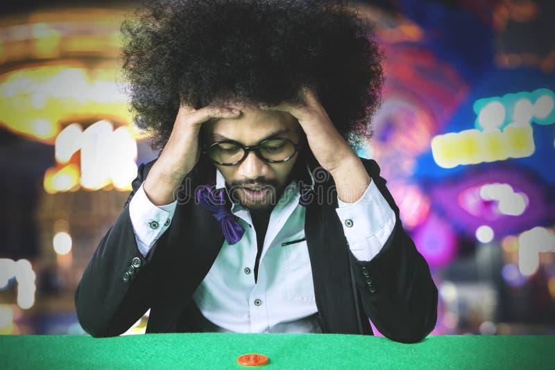 Frustrerad hasardspelareman som förlorar på en vågspel arkivbild