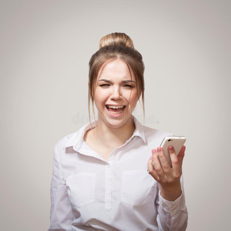 Frustrerad kvinna med telefonen royaltyfri foto