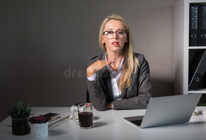 Frustrerad kvinna som sent arbetar på kontoret arkivbild