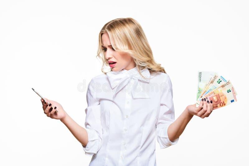 Frustrerad kvinna som ser i misstro på hennes mobiltelefon som rymmer påfyllningar av eurosedlar mot vit bakgrund fakturera telef royaltyfri fotografi