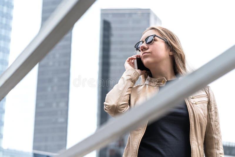 Frustrerad kvinna som talar på telefonen i staden arkivbild