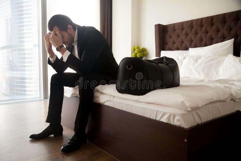 Frustrerad man i dräktsammanträde på säng förutom bagagepåse arkivfoton