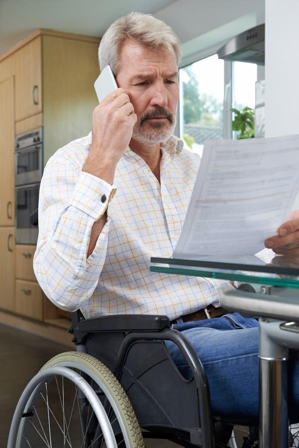 Frustrerad man i stunden läsande Le för rullstoldanandepåringning arkivfoton