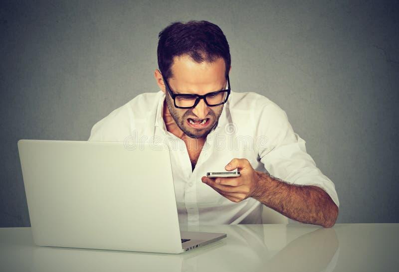 Frustrerad man med bärbara datorn som smsar på mobiltelefonen royaltyfri fotografi