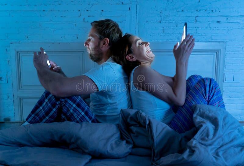 Frustrerad man och hemfallna kvinnapar genom att använda mobiltelefoner i säng på natten som ignorerar sig royaltyfri fotografi