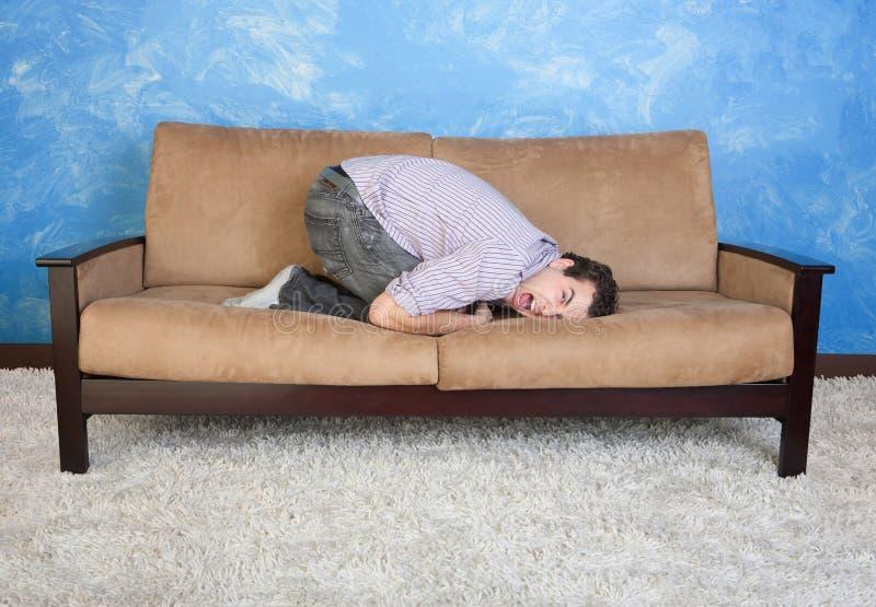 Frustrerad man på sofaen royaltyfri fotografi